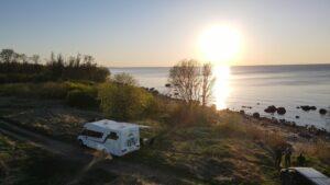 matkaauto mere ääres päikeseloojang drooni pilt